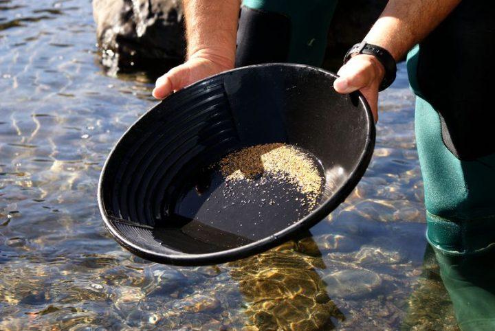 orpailleur professionnel avec un pan et beaucoup de paillettes d'or