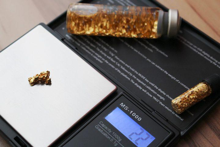 fioles de paillettes d'or et pépite d'or sur une balance